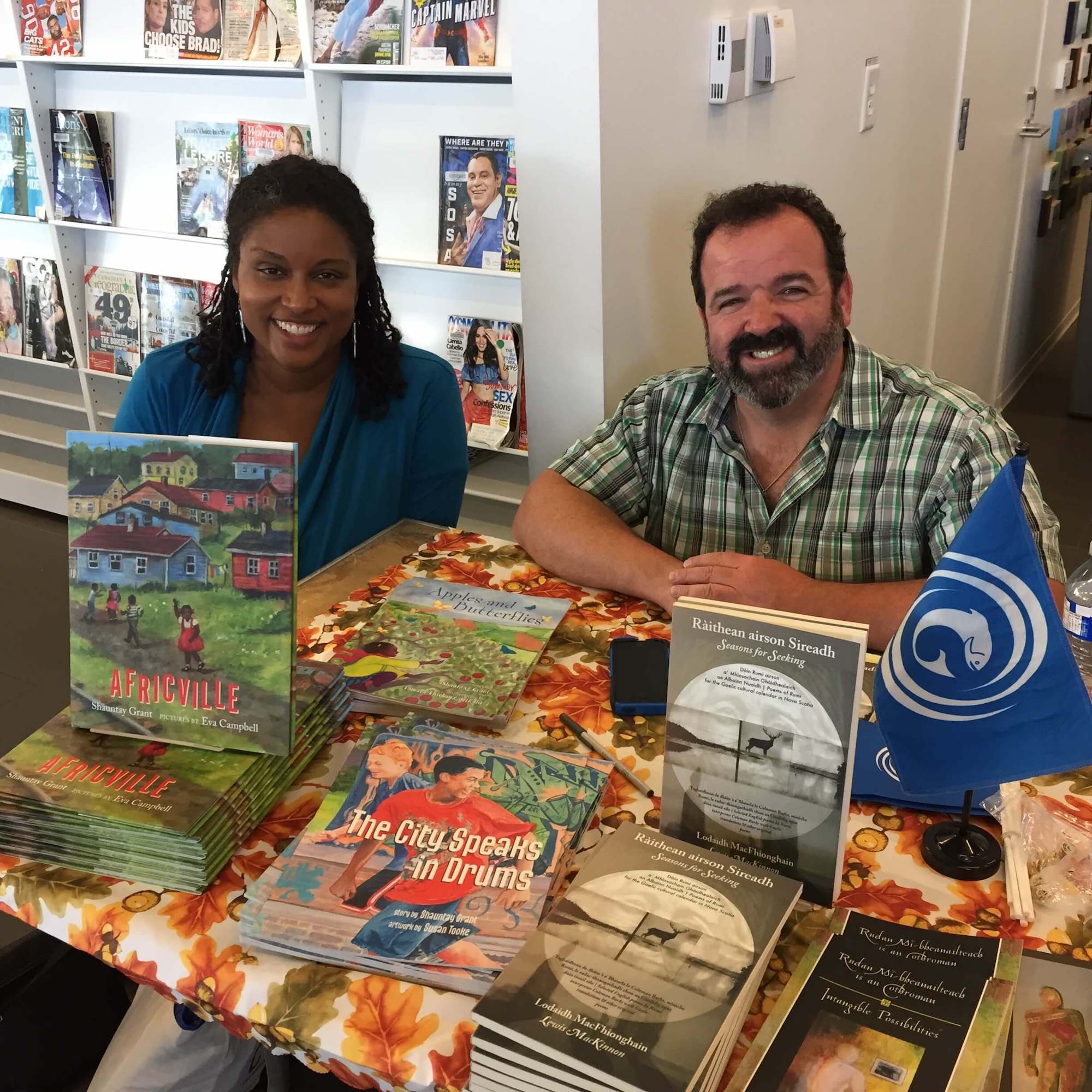 House of Anansi author Shauntay Grant and Bradan Press author Lewis MacKinnon (Lodaidh MacFhionghain) signing books at Word on the Street Halifax 2018